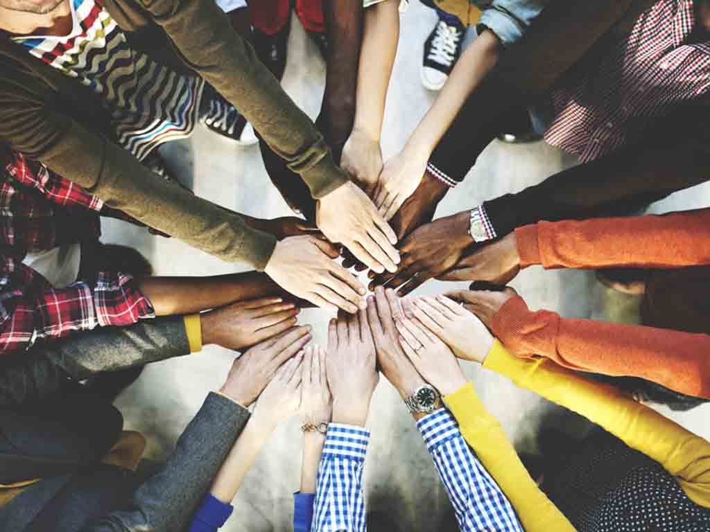 A group of people sticking their hand in the middle as a team.